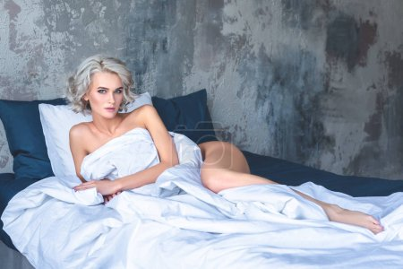 seductive young woman lying in bed covered with white blanket