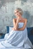 """Постер, картина, фотообои """"привлекательный молодой женщины, сидя на кровати покрыты белым одеялом"""""""