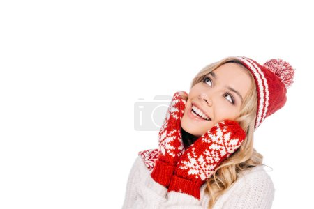 beautiful smiling young woman in red hat and mittens looking up isolated on white