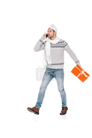 man in sweater, scarf and hat holding gift box and talking by smartphone isolated on white