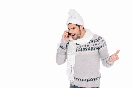 emotional young man in winter outfit yelling by smartphone isolated on white