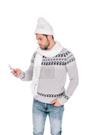 young man in sweater, scarf and hat standing with hand in pocket and using smartphone isolated on white