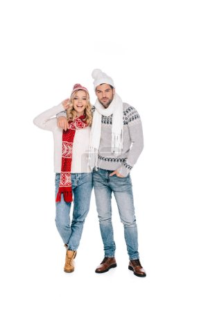 beautiful happy young couple in sweaters, scarves and hats standing together and looking at camera isolated on white