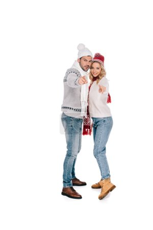 full length view of beautiful young couple in winter outfit standing together and pointing at camera isolated on white