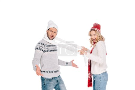 smiling young woman holding scarf around neck of young man looking at camera isolated on white