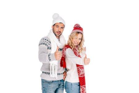 Photo pour Beau jeune couple en tenue d'hiver montrant les pouces vers le haut et souriant à la caméra isolé sur blanc - image libre de droit