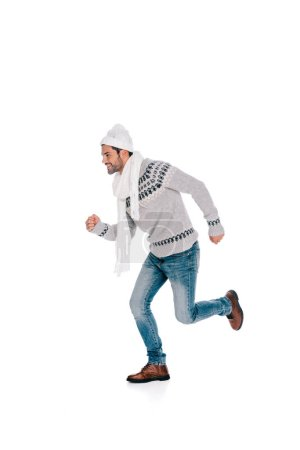smiling young man in sweater, scarf and hat running and looking away isolated on white