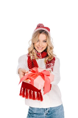 beautiful young woman in scarf and hat holding gift box and smiling at camera isolated on white