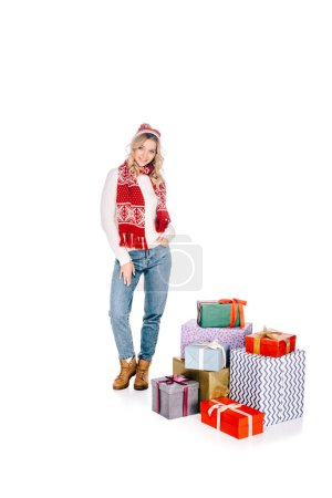 beautiful young woman in scarf and hat standing near stacked gift boxes and smiling at camera isolated on white