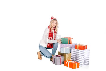beautiful young woman in scarf and hat crouching near stacked gift boxes and smiling at camera isolated on white