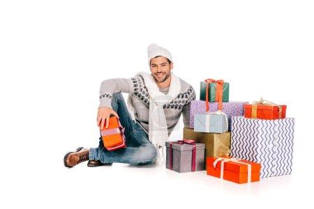 Foto de Hombre guapo en la bufanda y el sombrero sentado cerca de cajas de regalo y sonriendo a cámara aislada en blanco - Imagen libre de derechos
