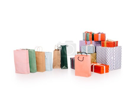 colorful shopping bags and various stacked gift boxes isolated on white