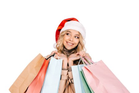 beautiful smiling young woman in santa hat holding shopping bags and looking away isolated on white