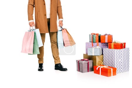 cropped shot of man holding shopping bags and standing near gift boxes isolated on white