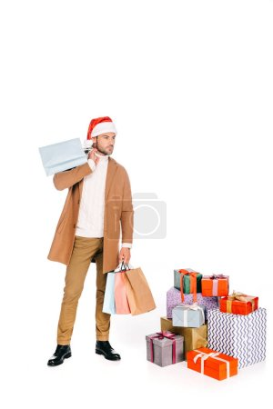 young man in santa hat holding shopping bags while standing near gift boxes isolated on white