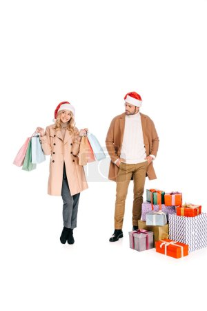 Foto de Hombre joven en santa sombrero de pie cerca de Navidad presenta y mirando sonriente chica sosteniendo bolsas aisladas en blanco - Imagen libre de derechos