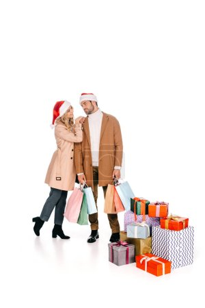beautiful young couple in santa hats looking at each other while standing with shopping bags near christmas presents isolated on white