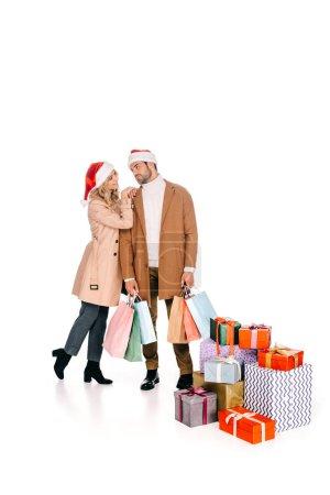 beau jeune couple en chapeaux santa regardent en se tenant debout avec des sacs à provisions près de Noël présente isolé sur blanc