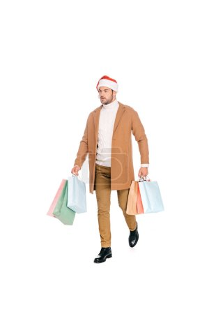 full length view of young man in santa hat holding shopping bags and walking isolated on white
