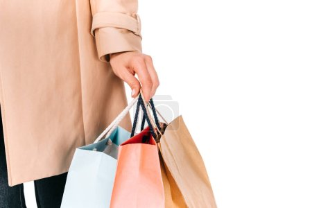 close-up partial view of young woman holding shopping bags isolated on white