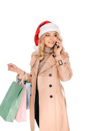 Photo pour Belle jeune femme souriante au chapeau de santa holding sacs à provisions et de parler de smartphone isolé sur blanc - image libre de droit
