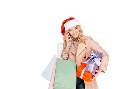Foto de Sonriente a mujer joven con sombrero de santa con cajas de regalo, bolsas de compras y hablando por teléfono inteligente aislaron en blanco - Imagen libre de derechos