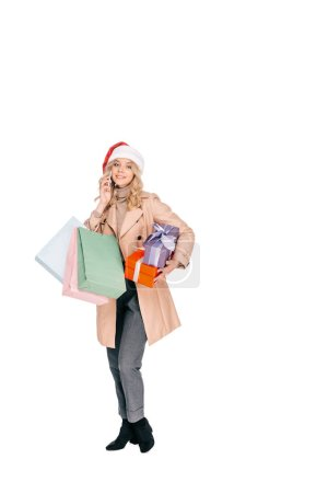 Photo for Beautiful smiling young woman in santa hat holding gift boxes, shopping bags and talking by smartphone isolated on white - Royalty Free Image