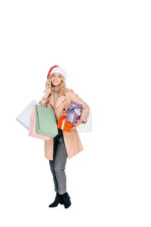 Foto de Hermosa joven sonriente con sombrero de santa sosteniendo cajas de regalo, bolsas de compras y hablar por teléfono inteligente aislado en blanco - Imagen libre de derechos