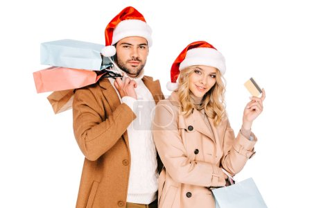 young couple in santa hats holding credit card and shopping bags isolated on white