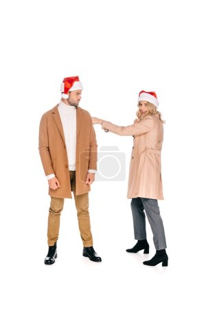 full length view of young couple in santa hats having fun together isolated on white