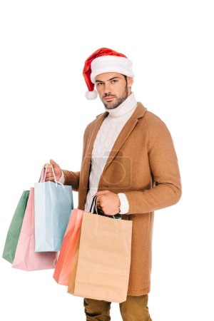 handsome young man in santa hat holding shopping bags and looking at camera isolated on white