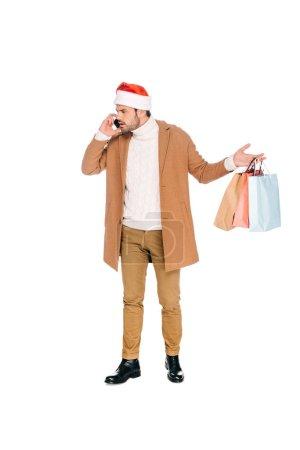 Photo pour Émotionnel jeune homme au chapeau de santa holding sacs à provisions et de parler de smartphone isolé sur blanc - image libre de droit