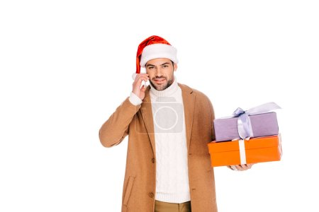 young man in santa hat holding gift boxes and talking by smartphone isolated on white