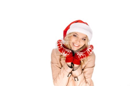 beautiful young woman in santa hat and mittens smiling at camera isolated on white