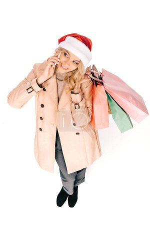 Photo for High angle view of happy young woman in santa hat holding shopping bags and talking by smartphone isolated on white - Royalty Free Image