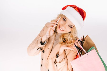 Photo for High angle view of beautiful smiling young woman in santa hat holding shopping bags and talking by smartphone isolated on white - Royalty Free Image
