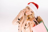 high angle view of beautiful smiling young woman in santa hat holding shopping bags and talking by smartphone isolated on white