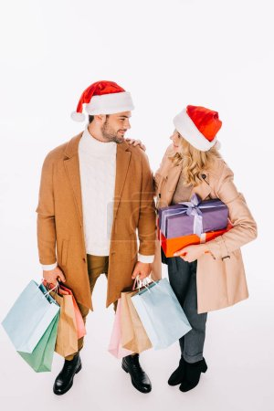 high angle view of young couple in santa hats holding presents and shopping bags isolated on white
