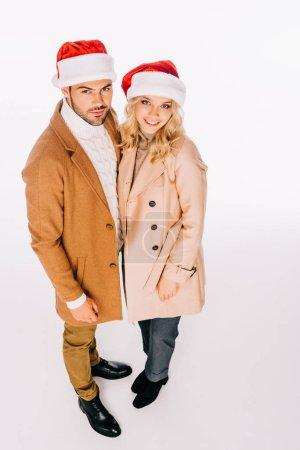 Foto de Vista de ángulo alto de hermosa pareja jóvenes con sombreros de santa sonriendo a cámara aislada en blanco - Imagen libre de derechos