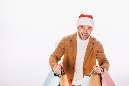 Photo pour Heureux jeune homme dans santa chapeau tenant des sacs à provisions et souriant à la caméra isolé sur blanc - image libre de droit