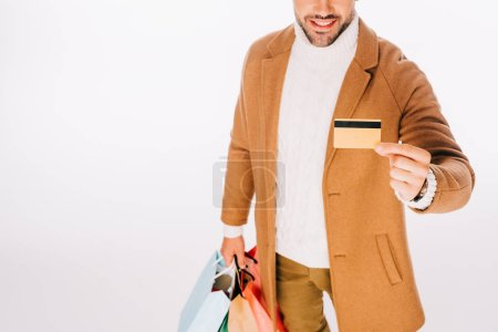cropped shot of happy young man holding credit card and shopping bags isolated on white