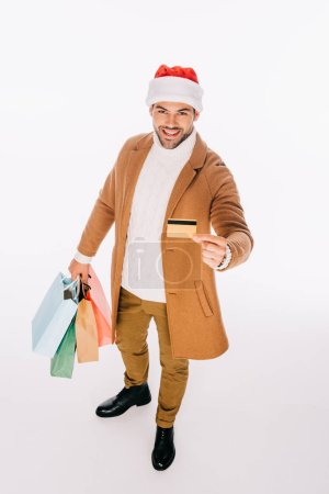 high angle view of smiling young man in santa hat holding credit card and shopping bags isolated on white