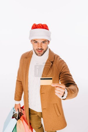 young man in santa hat holding credit card and shopping bags isolated on white