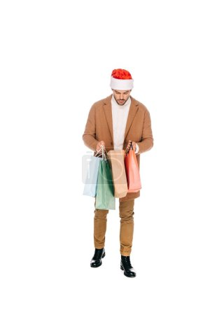 full length of young man in santa hat holding shopping bags isolated on white