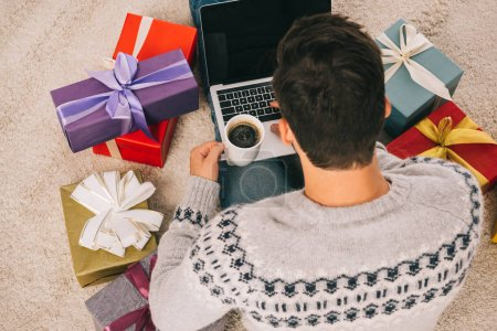 high angle view of man with cup of coffee sitting between gift boxes and using laptop with blank screen