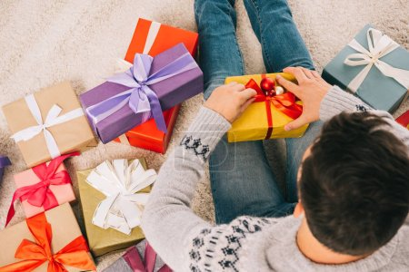 overhead view of young man sitting on carpet and opening christmas present
