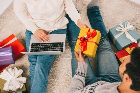 Photo for Cropped shot of couple holding gift box and woman using laptop - Royalty Free Image