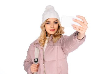 beautiful young woman with backpack taking selfie with smartphone isolated on white