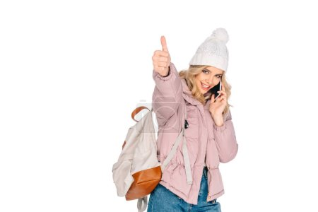 smiling young woman with backpack talking by smartphone and showing thumb up isolated on white