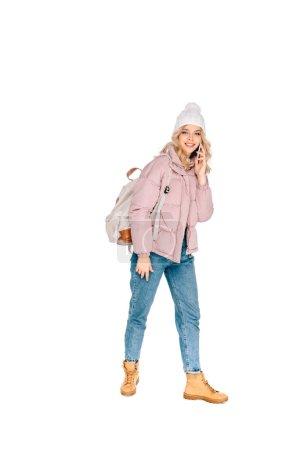 Foto de Hermosa joven viajero con mochila hablando por teléfono inteligente y sonrisa en cámara aislada en blanco - Imagen libre de derechos